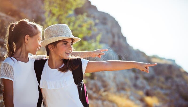 享受徒步游览的两个女孩对山 免版税库存照片