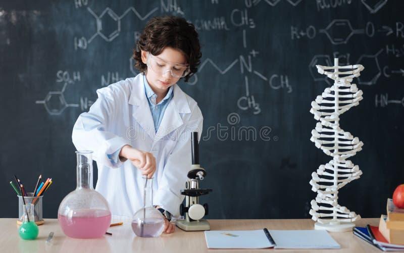 享受微生物学课的被集中的小研究员在实验室里 库存图片