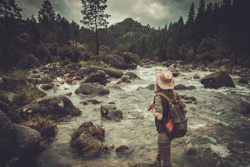 享受惊人的风景的妇女远足者临近狂放的山河 免版税库存照片