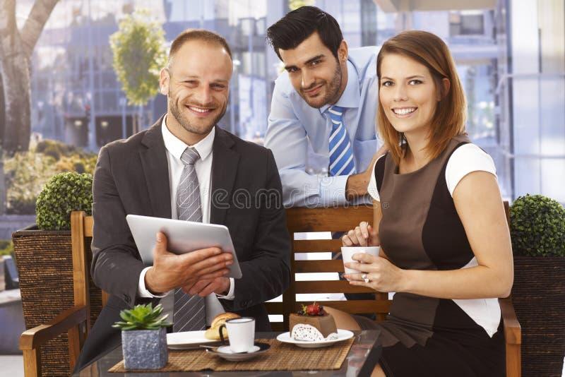 享受成功的愉快的企业队在早餐 图库摄影