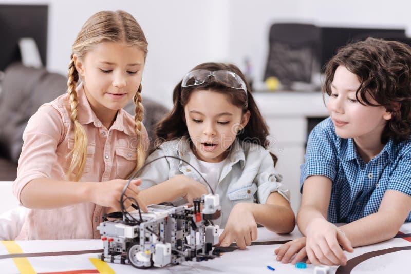 享受技术的高兴矮小的科学家在学校分类 免版税库存图片