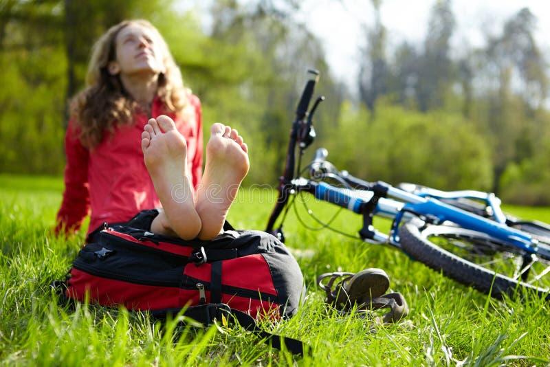 享受放松的愉快的女孩骑自行车者赤足坐在春天公园 免版税图库摄影