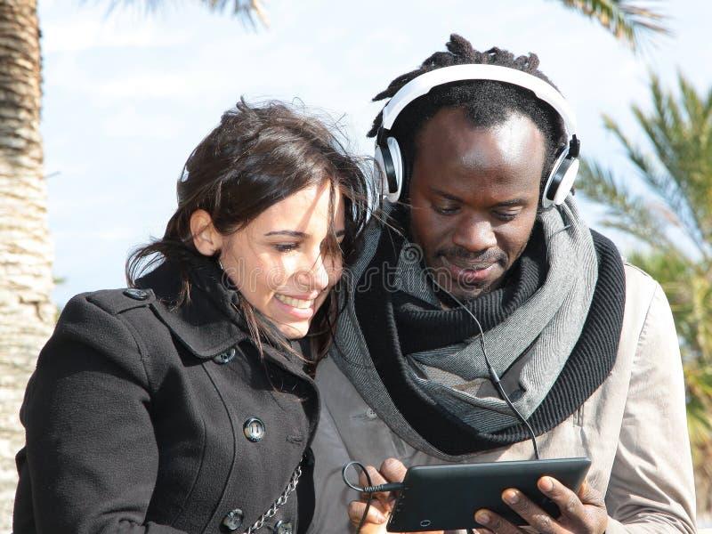 享受新技术的不同的种族夫妇  免版税图库摄影