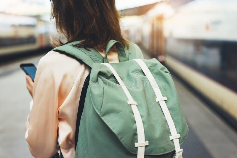 享受旅行 等待在有背包的驻地平台的年轻行家妇女在背景电车使用智能手机 免版税库存图片