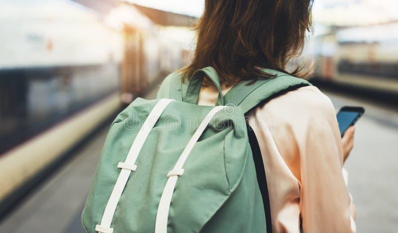 享受旅行 等待在有背包的驻地平台的年轻行家妇女在背景电车使用智能手机 图库摄影