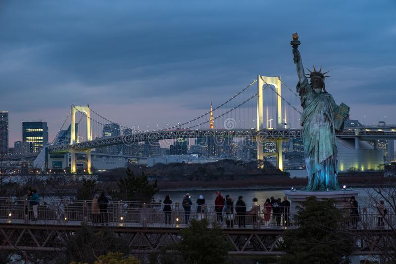 享受日本自由女神象和彩虹桥梁的看法游人在蓝色小时 免版税库存图片