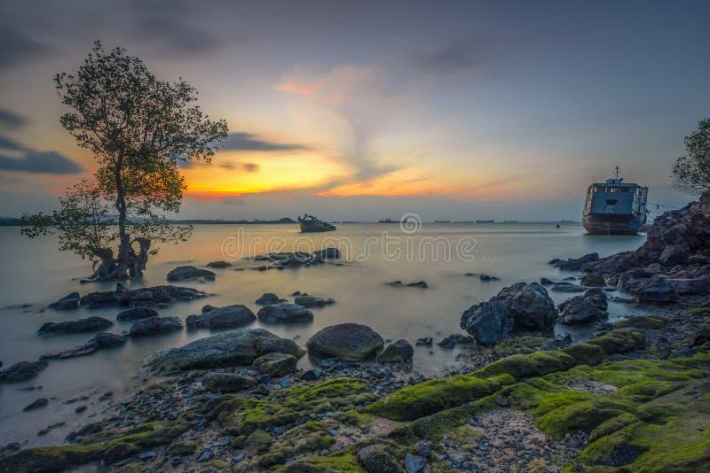 享受日落在岩石边缘 免版税库存图片