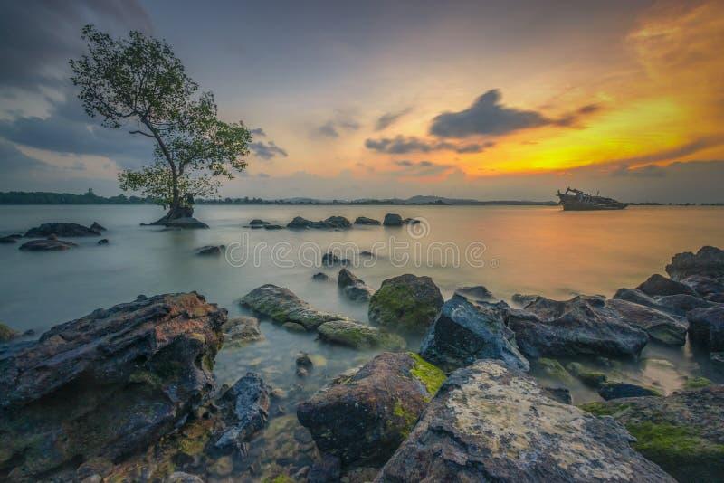 享受日落在岩石边缘 免版税库存照片