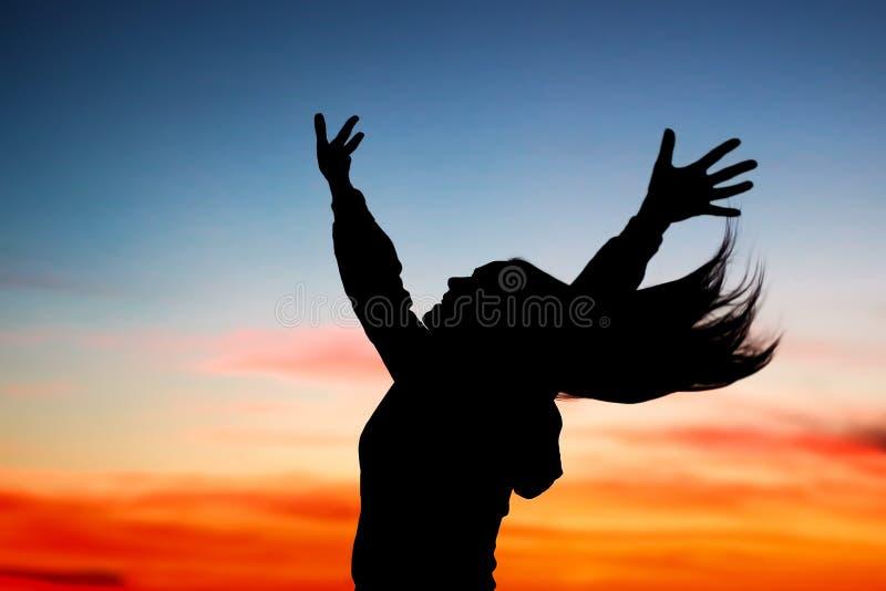 享受日落的愉快的妇女 免版税库存图片