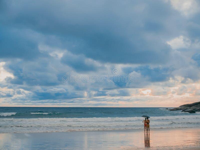 享受日落的美好的年轻夫妇 波浪在印度洋 免版税库存照片