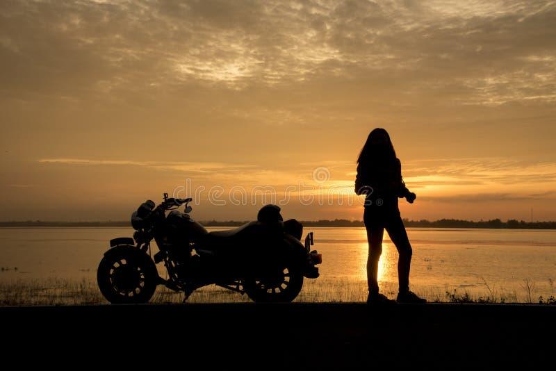 享受日落,女性骑马摩托车的美丽的妇女骑自行车的人 旅行摩托车的司机世界,放松在长的旅行以后, f 免版税库存照片