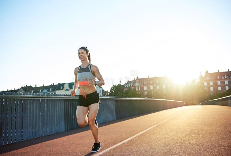 享受早晨奔跑的运动少妇 免版税图库摄影