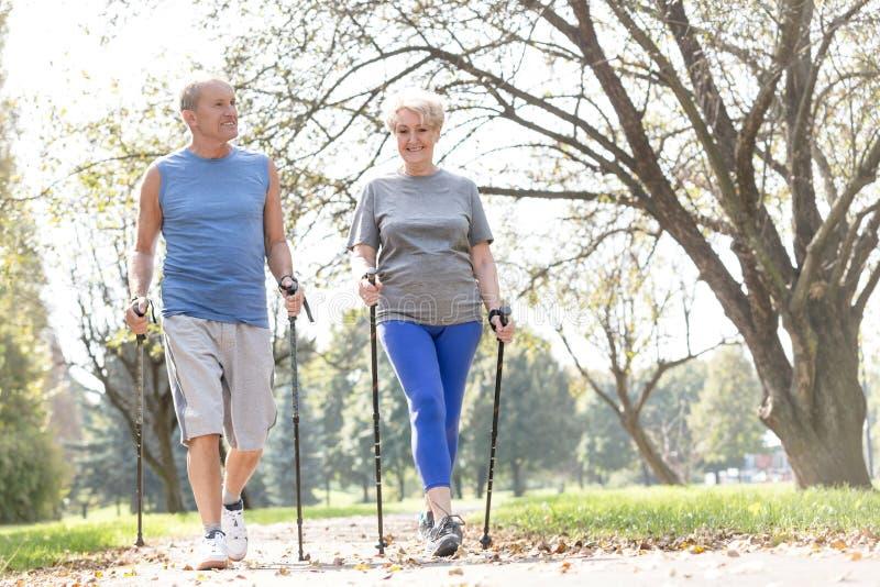 享受早晨步行的微笑的资深夫妇在公园 库存照片