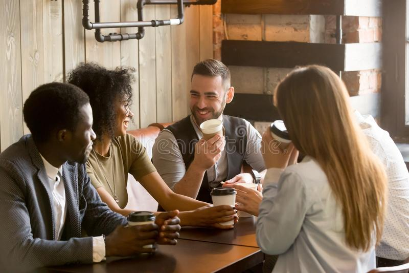 享受时间的微笑的朋友一起喝咖啡在咖啡馆 免版税图库摄影