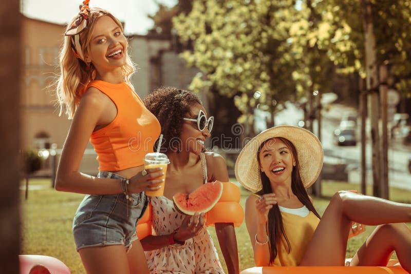 享受时间的活跃三个女朋友在野餐期间户外 库存图片