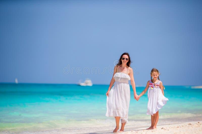 享受时间的母亲和小女儿在热带海滩 免版税库存图片