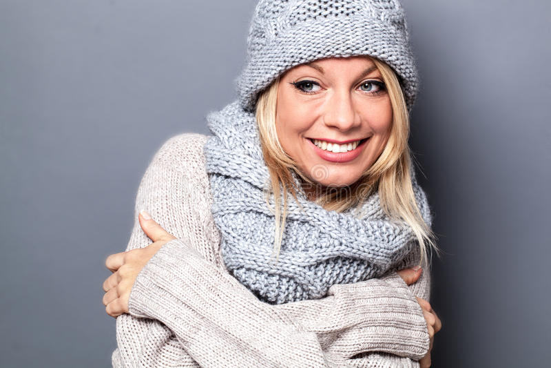 享受时兴的软的羊毛冬天的微笑的年轻白肤金发的妇女 免版税图库摄影