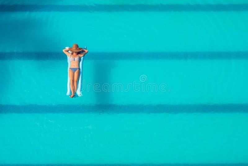 享受晒黑 美丽的概念池假期妇女年轻人 亭亭玉立的少妇顶视图比基尼泳装的在大游泳池的蓝天床垫 免版税库存图片