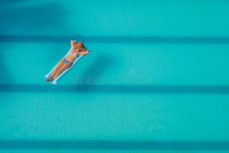 享受晒黑 美丽的概念池假期妇女年轻人 亭亭玉立的少妇顶视图比基尼泳装的在大游泳池的蓝天床垫 免版税图库摄影