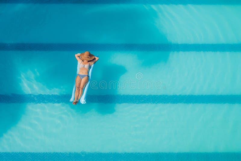 享受晒黑 美丽的概念池假期妇女年轻人 亭亭玉立的少妇顶视图比基尼泳装的在大游泳池的蓝天床垫 库存图片