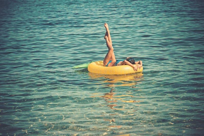 享受晒黑 E 亭亭玉立的年轻女人顶视图拿着黄色气垫的比基尼泳装的 免版税库存照片