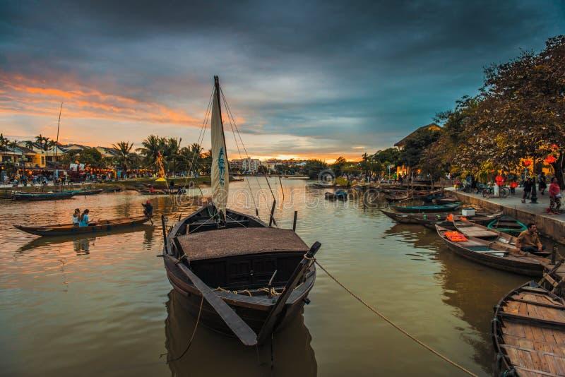 享受晚上的本机和游人,由会安市河 免版税图库摄影