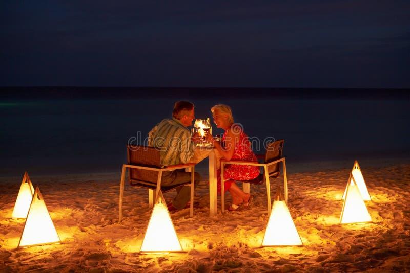 享受晚膳食的资深夫妇在室外餐馆 免版税库存照片