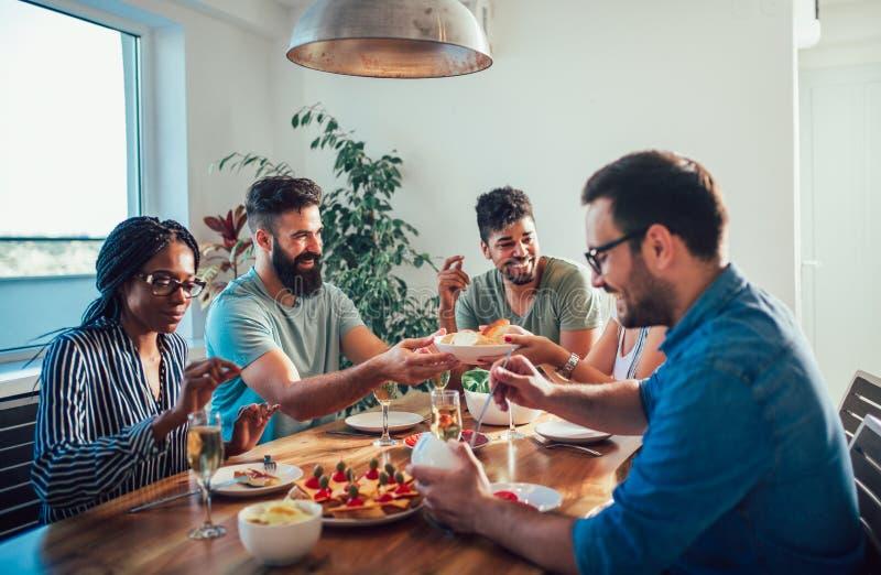 享受晚餐会的小组不同种族的朋友 免版税库存照片