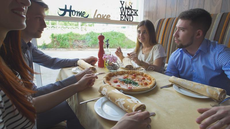 享受晚餐和停留在餐馆的年轻愉快的朋友 免版税库存照片