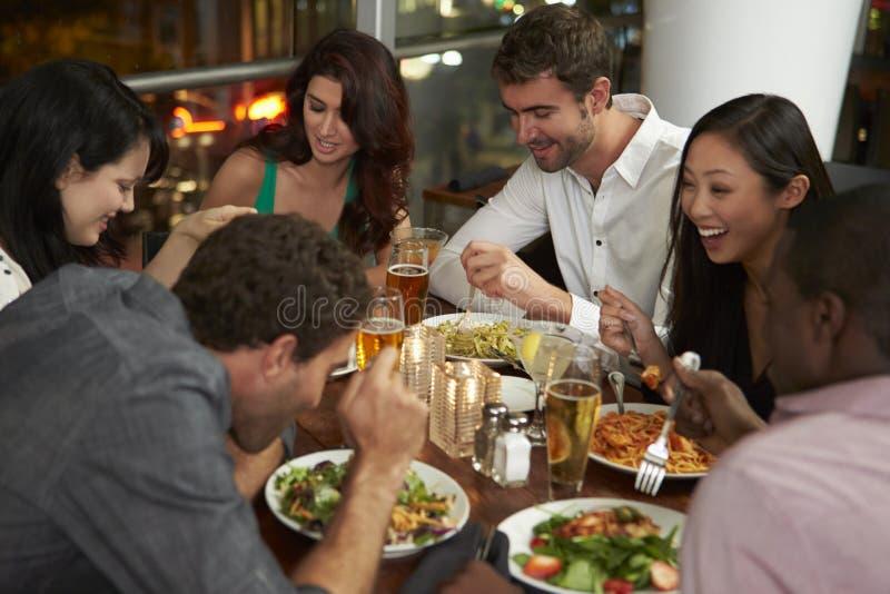 享受晚餐的小组朋友在餐馆 免版税图库摄影