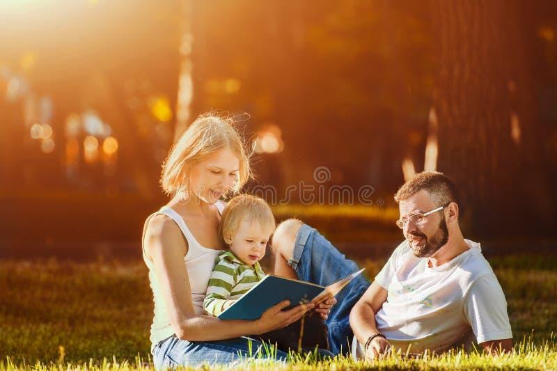 享受晴天在公园,父母教儿子的愉快的家庭如何读 免版税库存图片