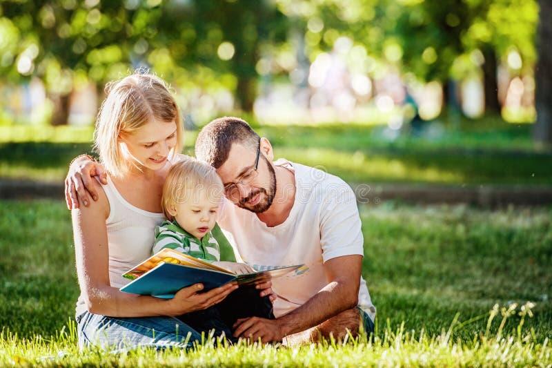 享受晴天在公园,父母教儿子的愉快的家庭如何读 免版税图库摄影