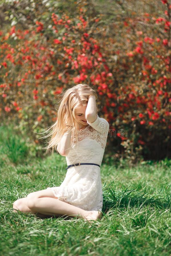 享受晴天的美丽的少妇在公园在开花季节期间在一个好春日 免版税库存照片