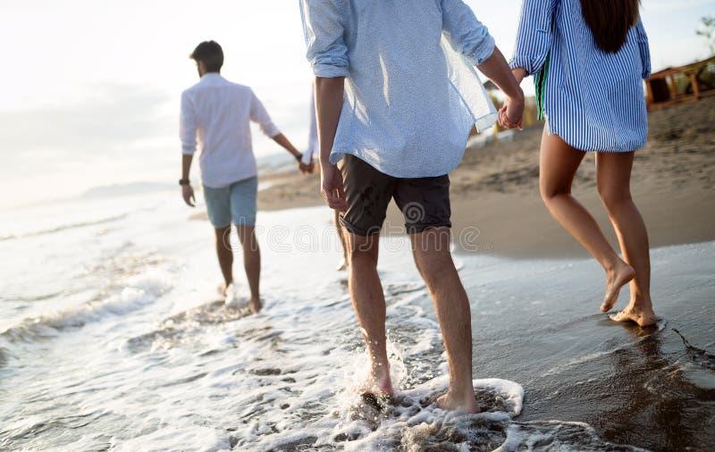 享受暑假的小组朋友在海滩的日落 图库摄影