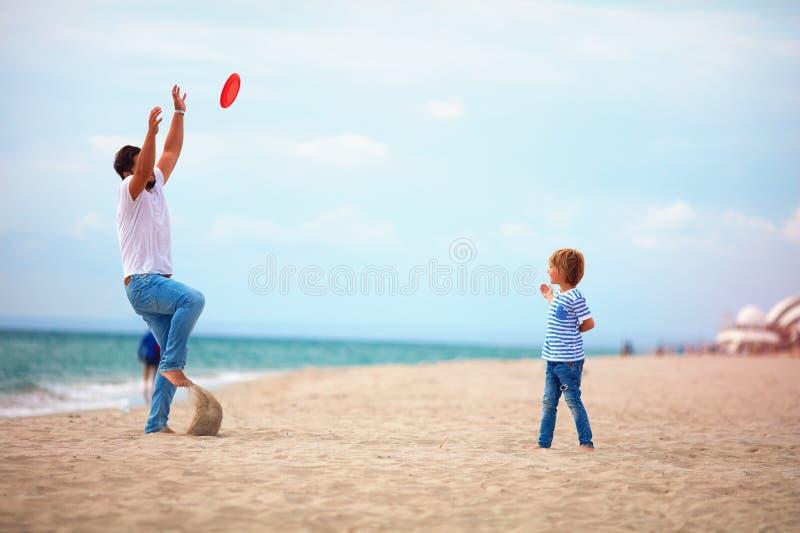 享受暑假的父亲和儿子,打海滩活动比赛在海附近,家庭投掷的飞行盘 库存照片