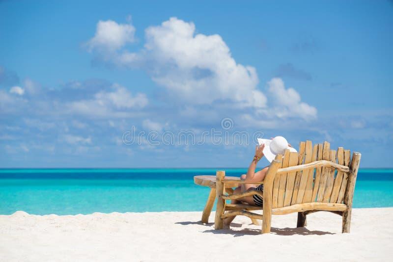 享受暑假,海滩的年轻美丽的妇女放松,求和 库存照片