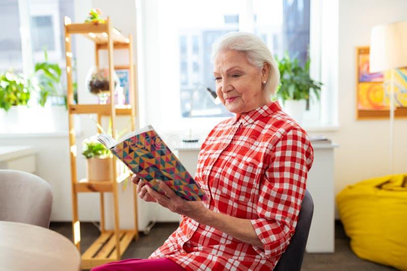 享受有趣故事的快乐的年迈的妇女 免版税库存照片