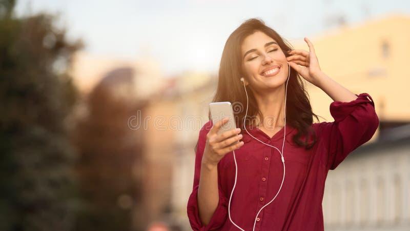 享受歌曲 与闭合的眼睛的女孩听的音乐户外 库存图片
