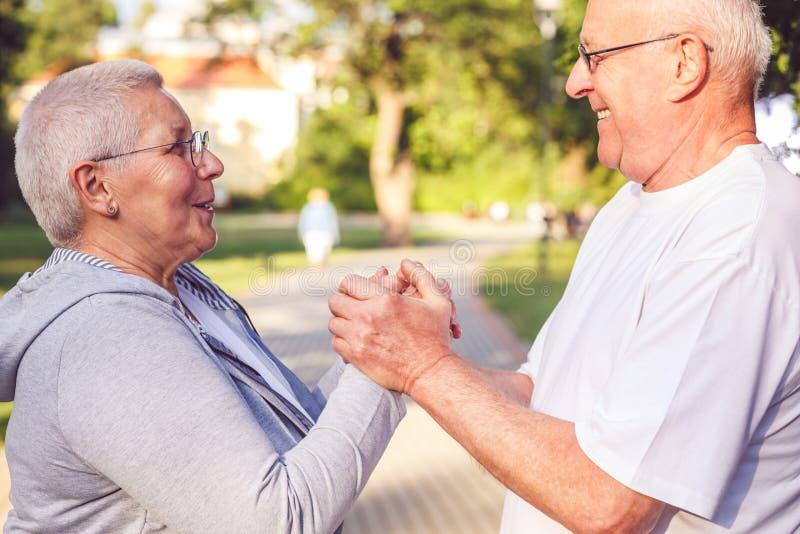 享受步行的愉快的一起-浪漫领抚恤金者夫妇在公园 免版税库存图片