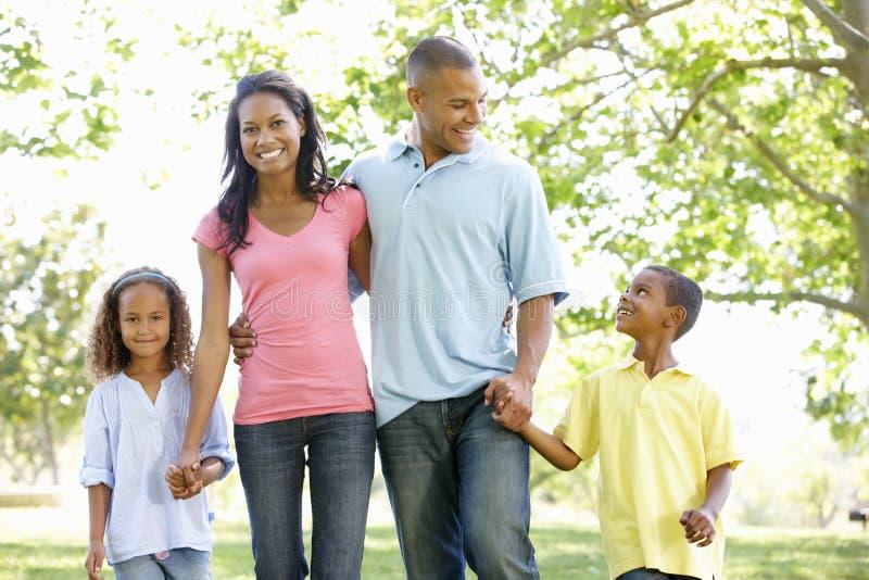 享受步行的年轻非裔美国人的家庭在公园 免版税库存图片