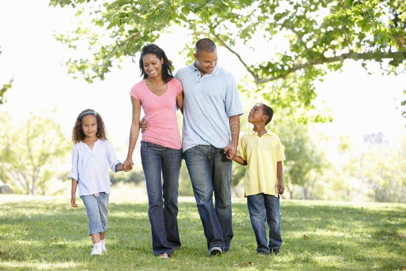 享受步行的年轻非裔美国人的家庭在公园 库存照片