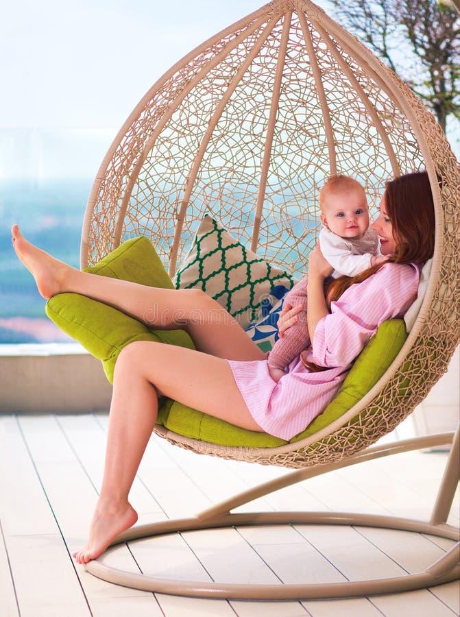 享受母道的愉快的年轻女人,在摇摆坐夏天露台 库存图片