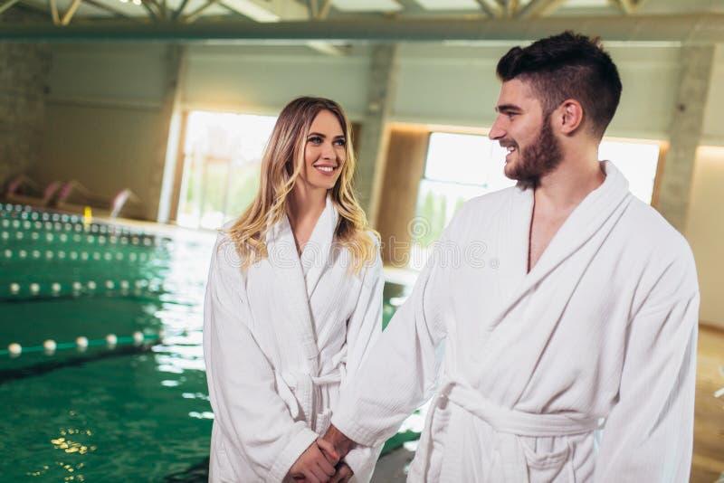 享受治疗和放松在健康温泉中心的年轻夫妇 免版税库存图片