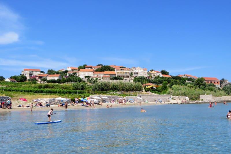 享受沿Lumbarda海滩沙滩的本机和游人一个美好的夏日在科尔丘拉岛,克罗地亚的 免版税库存照片