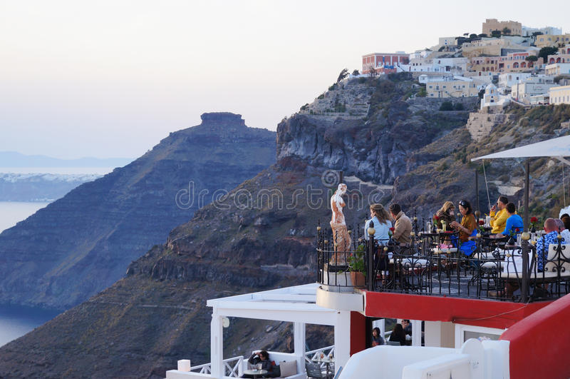 享受浪漫晚餐的游人在日落,圣托里尼,希腊期间 免版税库存照片