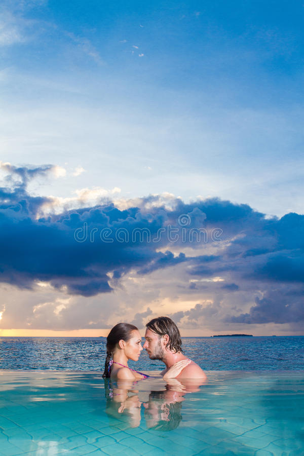 享受浪漫游泳的年轻夫妇 免版税库存照片