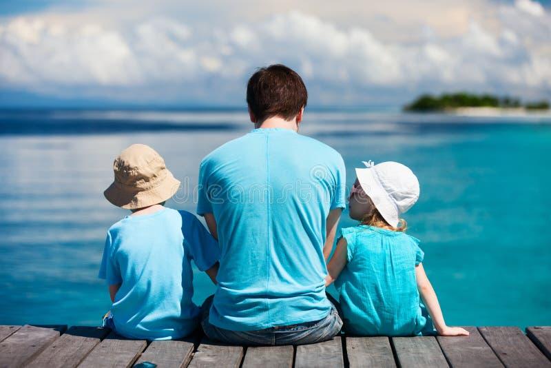 享受海景的父亲和孩子 免版税库存图片