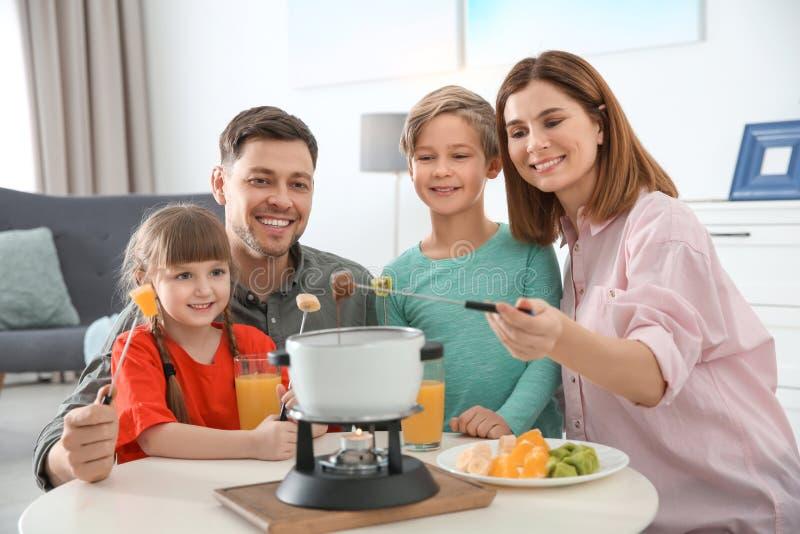 享受涮制菜肴晚餐的幸福家庭 免版税图库摄影