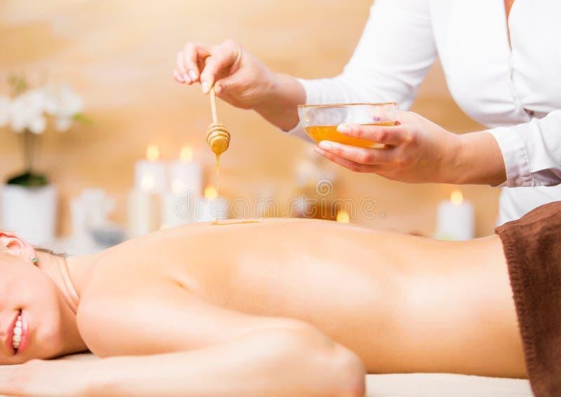 享受温泉治疗用蜂蜜的妇女 库存照片