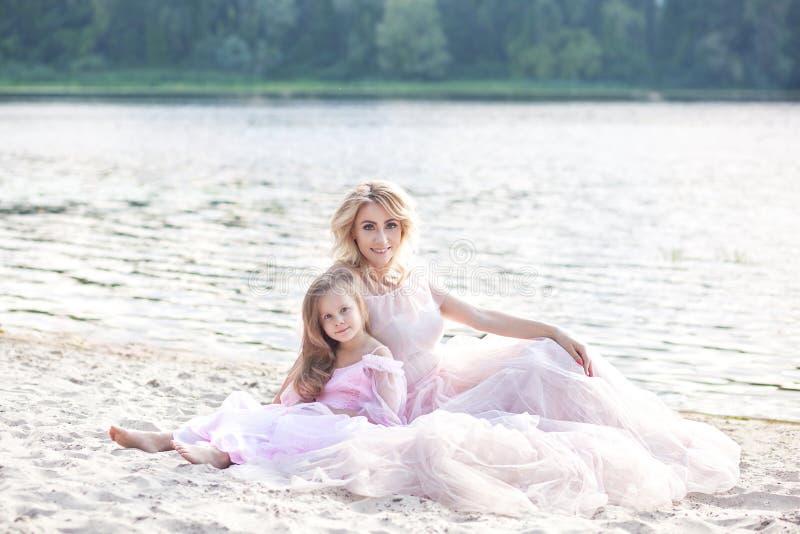 享受湖视图和放松在海滩的母亲和她的女孩在美丽的礼服的一好日子 家庭生活方式和 图库摄影